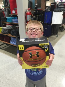Alex holds up his basketball for Santa